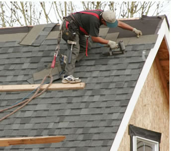 Man pulling shingles from a roof